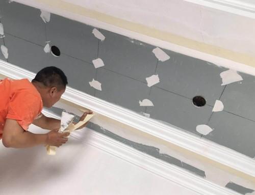 北京老房装修石景山鲁谷工地木工吊顶装修施工完成,油漆工正在处理石膏板接缝处和补钉眼